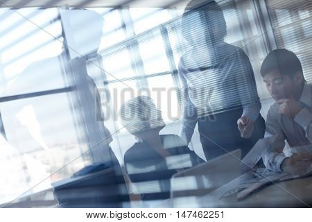 Working businesspeople behind glassy walls