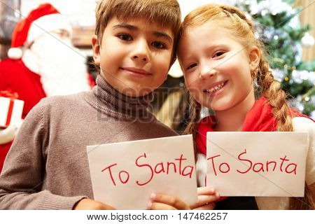 A portrait of two children holding papers with text To Santa looking at camera and smiling with Santa Claus in the background