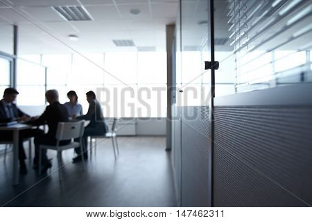 Dark office with people sitting at table aside