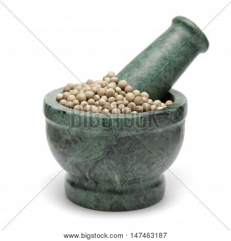 Organic White Pepper (Piper nigrum) on marble pestle. Isolated on white background.