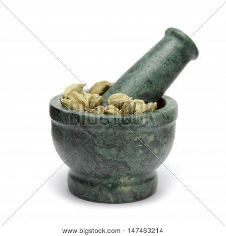 Organic Green or True cardamom (Elettaria cardamomum) on marble pestle. Isolated on white background.