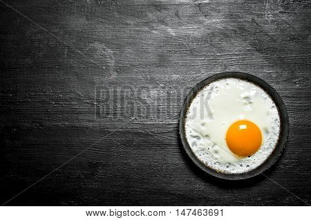 Fried egg in a frying pan. On a black wooden background.