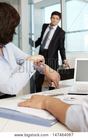 Manager pointing at her watch to entering employer