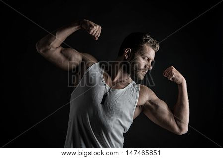 young handsome bearded man sexy macho bodybuilder with muscular hands and beard on serious face in white vest posing in studio on black background