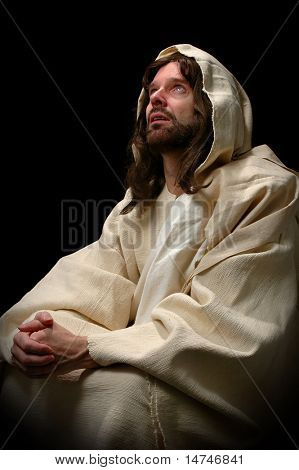 Jesus in prayer over a dark background