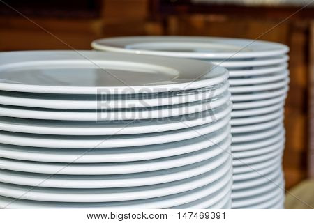 stack of white plates clean on buffet table at restaurant