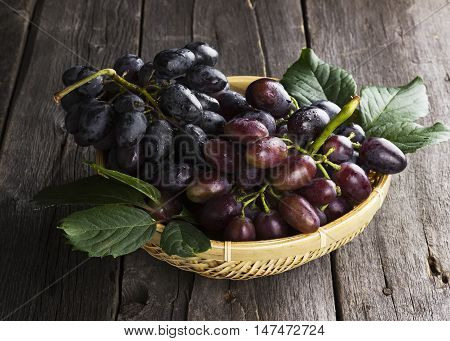 Clusters Of Dark Grapes In Wattled Bowl On A Wooden Background