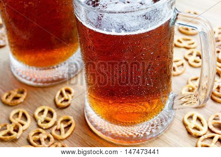 Mug of cold foamy beer with brezel. Traditional german Oktoberfest snacks and beer on wooden background