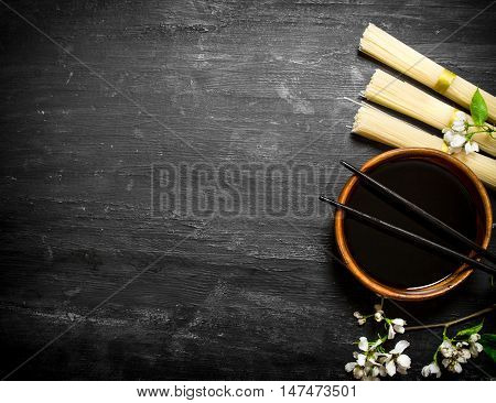 Dry noodles with soy sauce and the cherry branches.On a black wooden background.