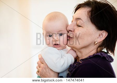 Grandmother is kissing her baby grandson - indoors scene