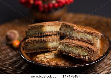Fresh Dutch filled spicy cookies with almonds on autumn colored and dark background