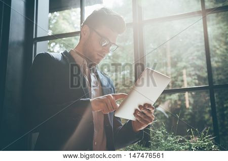 Concentrated on his new project. Low angle view of young man working on digital tablet while standing in front of the big window indoors