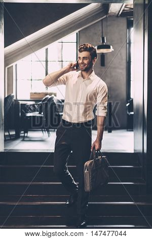 I will be in five minutes! Confident young man in smart casual wear talking on the mobile phone and smiling while holding bag and standing in office