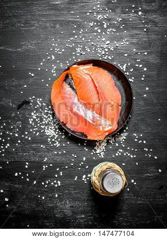 Thin slices of smoked salmon with salt. On the black chalkboard.