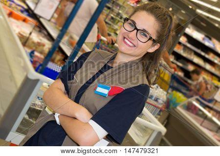 Smiling Supermarket Employee Standing Among Shelves -
