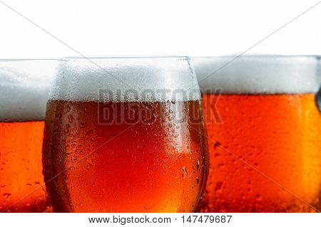 Few frosty glasses of cool beer foam covered with drops closeup. Isolated on white background.