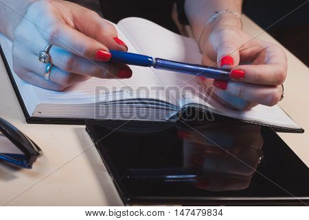 Blue pen in hand, the woman behind the Desk, the concept of a business woman
