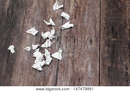 White paper sheet  note rip Pieces and crumpled on a wooden floor with copy space for add text above and may be used as background :