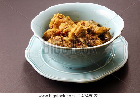 Spicy and aromatic Chicken curry in a bowl on a moody background