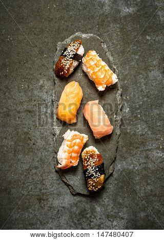 Japanese sushi with salmon, shrimp and eel. On the stone table.
