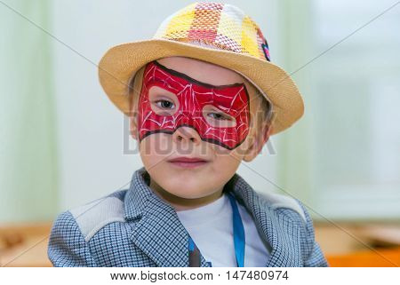 Caucasian boy with a straw hat and a spiderman mask on his face seriously looks at camera. Gangster-like expression.