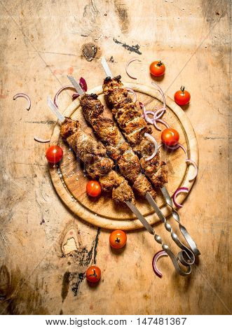 Shish kebab on skewers with tomato. On a wooden table.