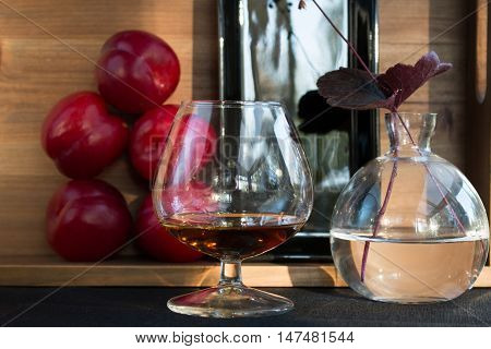 Plum liqueur in glass with plums closeup
