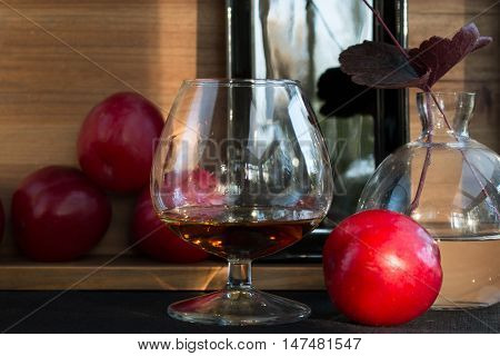 Plums and plum liqueur in glass closeup