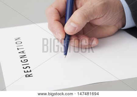 Man with a pen in the hand writing a letter of resignation on a table