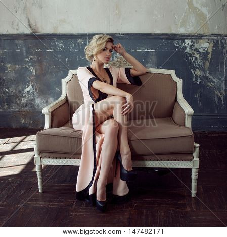 Fashion model with blond hair. Young attractive woman, siting on the sofa, vintage style