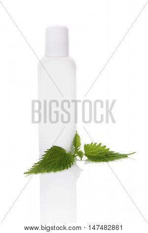 Stinging nettle cosmetics mockup. Fresh stinging nettle leaves and white plastic bottle without label isolated on white background.
