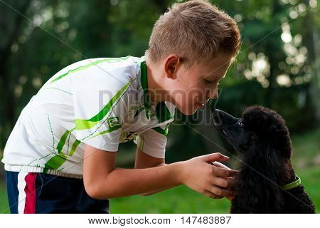 boy with a black poodle playing in nature summer day