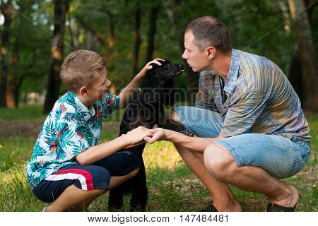 father and son and a black poodle in nature summer day