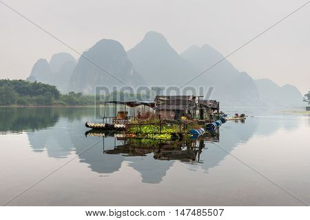 Yangshuo China - October 20 2013: Camping bamboo raft house on the Li river in the overcast nasty day in rural Yangshuo China.