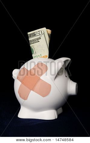 Piggy bank with bandages over a dark background