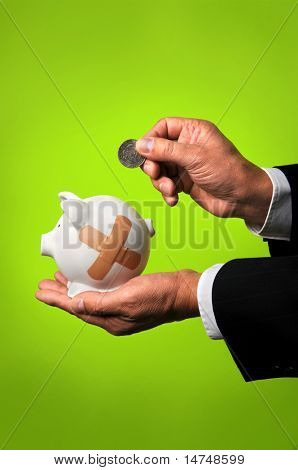 Businessman saving coin in piggy bank with bandages