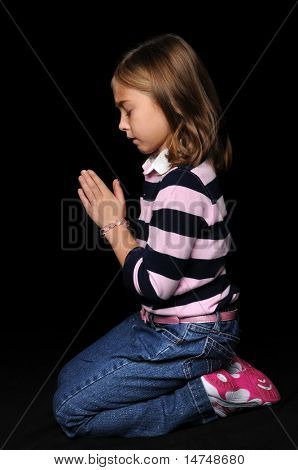 Portrait of young girl praying with hands together