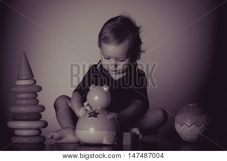Caucasian baby playing with a toy pyramid. Photo in vintage style of old pictures