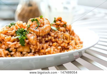 Tasty risotto with Shrimp, fresh herbs vegetables on a white plate.