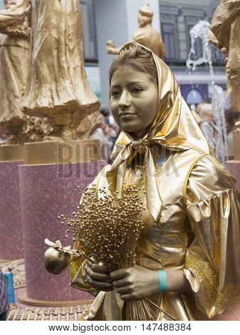 Moscow - September 10 2016: Beautiful Russian girl in a gold dress and gold make-up the statue depicts famous landmarks - Fountain Friendship of Peoples September 10 2016 Moscow Russia