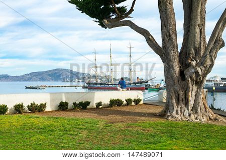San Francisco USA - September 24 2015: A man with dog looking at the vintage boats in the Maritime Nacional Historical Park