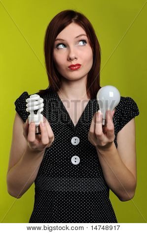 Woman holding fluorescent and incandescent light bulbs