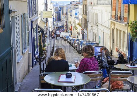 PARIS, FRANCE - MAY 12, 2015: Two unknown girls relax in one of the outdoor cafes on the slopes of Montmartre.