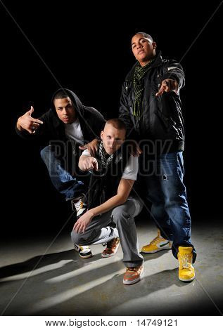 Hip hop dancers posing over a dark background