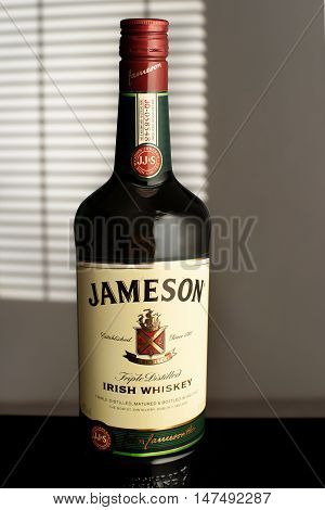 MINSK, BELARUS-AUGUST 25, 2016. Jameson is a blended Irish whiskey produced by the Irish Distillers subsidiary of Pernod Ricard. A bottle Jameson in the room illuminated by the light from the window