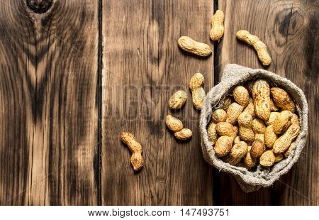 Peanuts in the old bag. On wooden background.