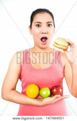 asian woman eatting a hamburger and many fruits