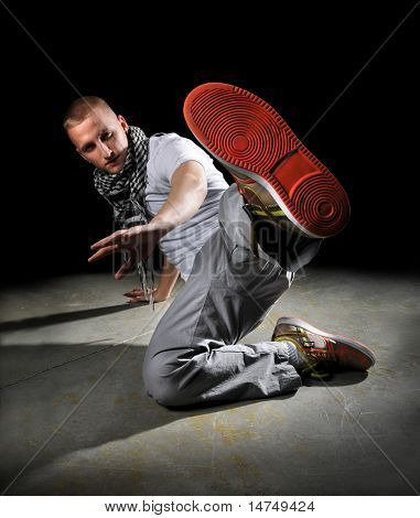 Hip hop dancer performing over a dark background with spotlight
