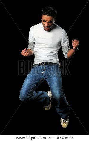 Young man jumping with fists clenched isolated over black