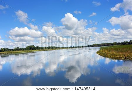 View from the Yahara River Trail gives glassy reflection of sky and clouds in the peaceful water of the River.